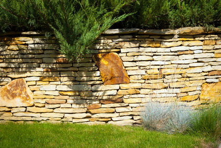 A stone wall in garden with bushes grass