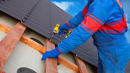 De arbeider van de mens gebruikt een machtsboor om een dakwerkbaan van het metaaldakwerk met schroeven te bevestigen.