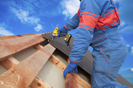 El trabajador utiliza un taladro eléctrico para fijar un trabajo de techo de metal con tornillos.