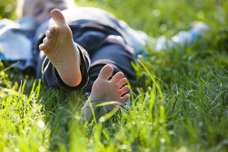 Happy little boy lying on green grass outdoors in spring park.