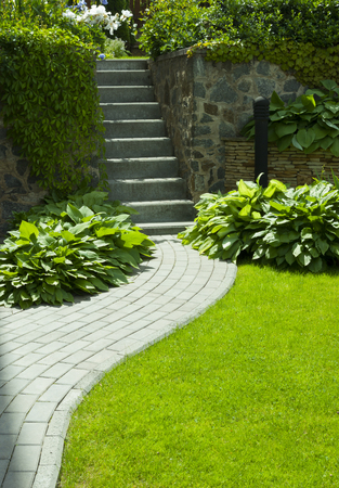 Garden stone path with grass growing up between the stones.Detail of a botanical garden. Stock Photo