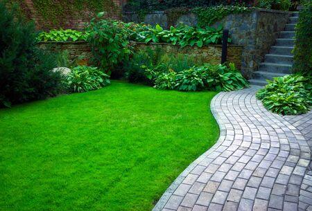 Camino de piedra del jardín con césped que crece entre las piedras. Detalle de un jardín botánico.