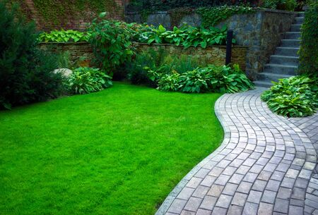 Gartensteinweg mit Gras, das zwischen den Steinen wächst. Detail eines botanischen Gartens.
