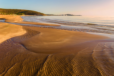 succession: Summer seascape.Gargano coast: bay of Vieste .- (Apulia) ITALY-Portonuovo beach is a succession of fine sand dunes, crossed by many little streams kars, That the visitors cool in the hot summer time.