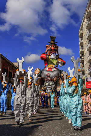 Putignano, Apulia, Italy - February 15, 2015: Carnival floats, giant paper mache. Carnival costume allegorical float of Ilva industry.Carnival laughs: the industry Ilva devours its workers. The Carnival of Putignano is Considered one of the most important