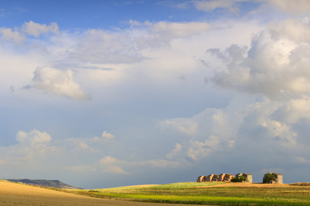 farmhouses: Between Apulia and Basilicata: farmhouses abandoned in a wheat fields.Italy.Summer: hilly rural landscape: farmhouses topped by clouds.
