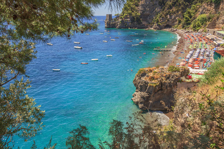 Summertime sescape: Amalfi Coast (Amalfi Coast) .The best beaches in Italy: Positano seaside (Campania) .Beach sets the cliff: a watchtower in the background.