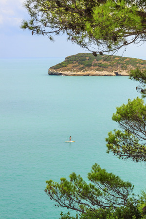 bather: Gargano coast: Fields of Baia beach, Vieste- (Apulia) ITALY-It is a picturesque bay framed by olive trees and pinewoods: the bather who practices standuppaddling and in the background the island fields. Stock Photo