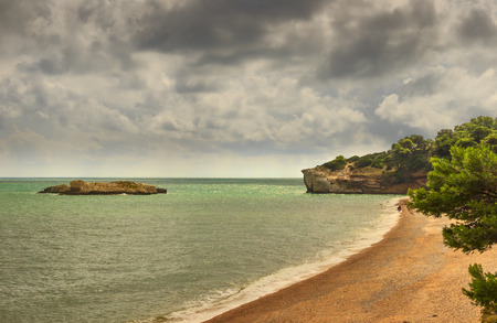 Gargano coast: Fields Bay beach, Vieste- (Apulia) ITAL- Walk on the Beach during a summer storm. The pebbly beach is sheltered bay to the south by the rock field, framed by olive trees and pinewoods.
