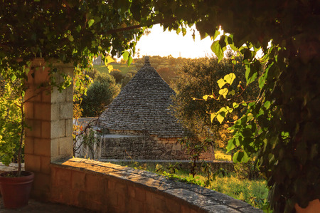 Italy landscape in Apulia countryside. Itria Valley, territory of Cisternino. Hills with olive trees and Trullo.Typical example of Apulian rural scenes. Porch overlooking lands at sunset.