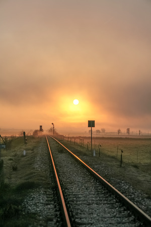 Winter sunrise reflected on the railroad.The beginning of a new day is lost at the vanishing point of the rails.Italy, Apulia.