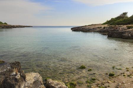 rocky coastline: Salento coast: Porto Selvaggio Bay.ITALY (Apulia) .Unspoiled nature with a small beach of sand and pebbles, surrounded by a rocky coastline. Stock Photo