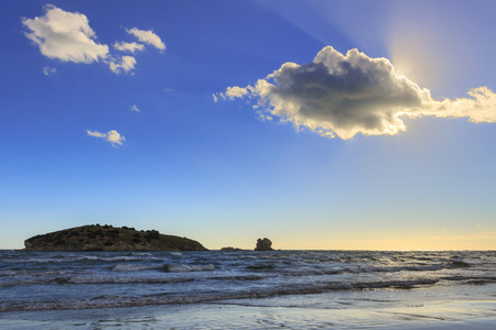 mare agitato: Gargano coast: Portonuovo beach, Vieste- (Apulia) ITALY.-Islet between waves dominated by cloud crossed by sunbeamsRays of sunshine peeking out from a cloud over a rough sea by waves and wind.