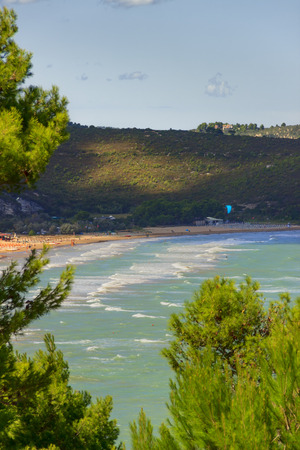 kiteboarding: The most beautiful coasts of Italy: Bay of Vieste (Apulia). Foreshortening of Portonuovo or Gattarella beach.Typical sandy beach of the Gargano coast .In the distance a tourist who makes kitesurfing.A windy day at sea on a sandy beach.