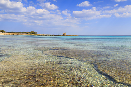 Italy summer seascape, Apulia coast: Marina di Lizzano beach (Taranto), Torretta bay. In the background Torre Sgarrata. The coastline is characterized by a suggestive alternation of sandy coves and jagged cliffs overlooking a truly clear and crystalline s Stock Photo