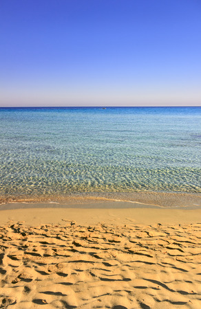 Summer seascape,Apulia coast: Marina di Pulsano beach (Taranto),  Lido Silvana bay.The coastline is characterized by a suggestive alternation of sandy coves and jagged cliffs overlooking a truly clear and crystalline sea (Italy).Lonely boat on the horizon