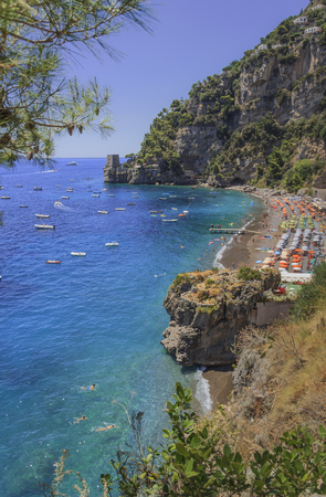 Summertime sescape: Amalfi Coast (Costiera Amalfitana).The best beaches in Italy:Positano seaside (Campania).Fornillo beach set in the cliff: the background a watchtower.Via a romantic walk, between the sea and the cliffs, beginning at Positano harbor, holidaymakers come to Fornillo beach: a well-established favorite amongst those searching for a more peaceful beach than that of Marina Grande. Stock Photo