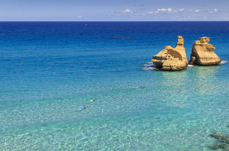 The most beautiful coast of Apulia: Torre DellOrso Bay, ITALY (Lecce).Typical seascape of Salento: view of the two stacks called The Two Sisters.Summertime: bathers swimming in the crystal clear sea.