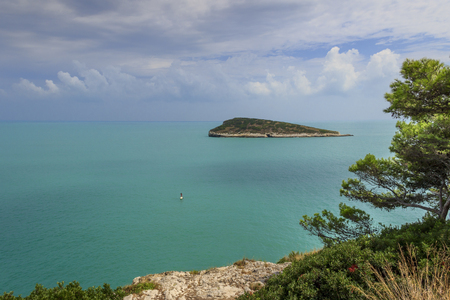Gargano coast: Campi Bay beach,Vieste-(Apulia) ITALY-It is a picturesque bay framed by olive trees and pinewoods:the bather who practices standuppaddling and in the background the islet Campi. 版權商用圖片