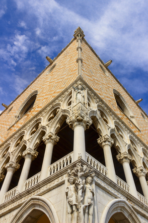 The Doges Palace in Venice: corner of the facade with angular sculptures. Its a palace built in Venetian Gothic style, Italy (Veneto).