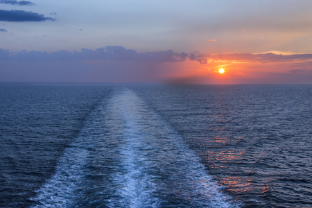 Sea horizon at sunset with ship wake. Visible trail, wake or path of a ship during the sundown. Romantic traveling evening.