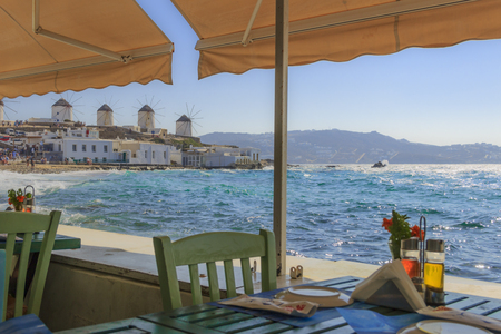 Mykonos, panoramic view of white famous windmills  Chairs with tables in typical Greek restaurant  of Little Venice in Cyclades island, Greece. 新聞圖片