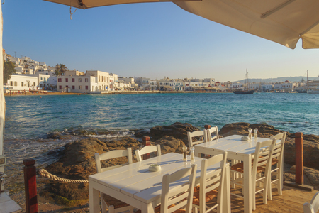 Mykonos, panoramic view of the marina,  sandy beach and the characteristic white houses. Chairs with tables in typical Greek restaurant  of old town, Cyclades island, Greece. 新聞圖片