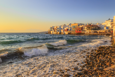 Sunset view of the famous pictorial Little Venice  in Mykonos island. Splashing waves over bars and restaurants of Mykonos old town, Cyclades, Greece.