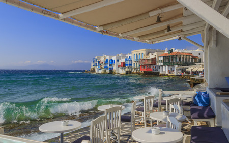 View of the famous pictorial Little Venice in Mykonos island. Splashing waves over bars and restaurants of  old town, Cyclades, Greece. Chairs with tables in typical Greek restaurant.