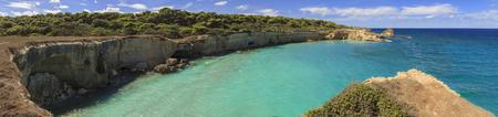 The most beautiful coast of Apulia: Torre Sant Andrea, Otranto , ITALY (Lecce).Typical coastline of Salento: view of Punticeddha beach. Seascape with cliffs, rocky arch and sea stacks (faraglioni).