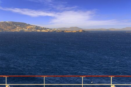 Panoramic view of Mykonos from cruise ship deck. Sea horizon in the wind: coast of Greece in the Aegean islands.Scenery of rocky coastline: azure waters of the Aegean Sea, cliff, rocks and stones.
