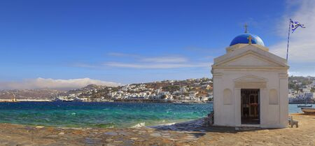 Whitewashed and blue domed Agios Nikolaos church in Mykonos, Greece, Europe. Panoramic view of old town and harbor: traditional greek village with white houses in Cyclades Islands.