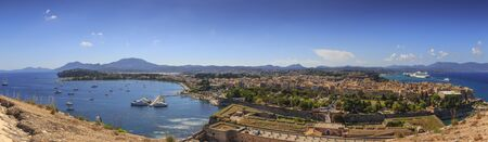 View of the ancient town on peninsula in to the crystal clear azure sea from Old Fortress of Corfu Town. Kerkyra, capital of Corfu island. Greece.
