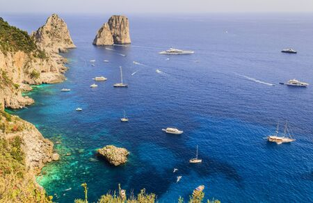 Panoramic view of famous Faraglioni Rocks, most visited travel attraction of Capri Island, Italy. Beautiful paradise landscape with azure sea in summer sunny day.