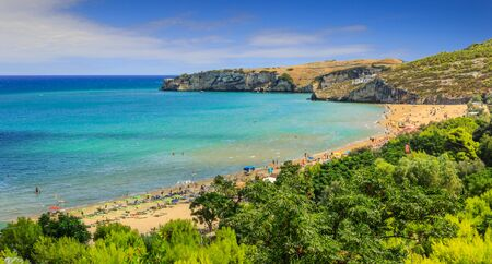 The most beautiful beaches of Apulia: San Nicola Bay,Peschici. Its surrounded by two rocks which dive in the sea, discloses a long stretch of golden and fine sand, perfect for pleasant strolls,Italy.