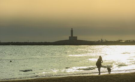 Gargano coast: bay of Vieste, (Apulia) Italy. Girl with dog walking on the sandy beach at dawn:in the background the Vieste Lighthouse. 写真素材