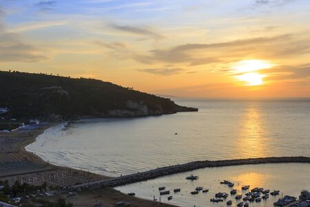 Panoramic view of the bay of Peschici at sunset: the marina and the sandy beach, Italy (Puglia). Peschici is famous for its seaside resorts, its territory belongs to the Gargano National Park.