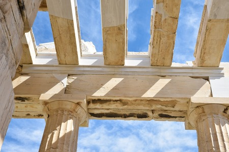 Roof structure and ceiling of Propylaea, monumental gateway Acropolis shown doric columns and architrave built with marble and limestone on blue sky background, Athens, Greece
