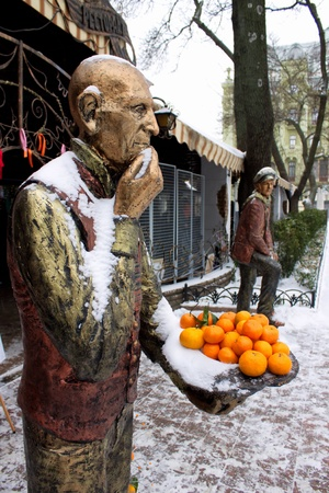 literary: Sculpture literary character with citrus in the hand
