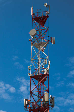 4G 5G cellular repeaters against a blue sky. Mobile phone Telecommunication Radio antenna Tower Banque d'images