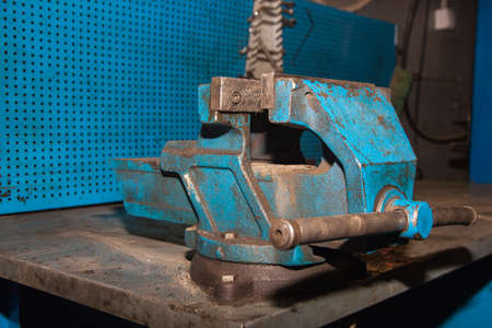 Old blue vise set on a workbench in a car repair shop. Device for clamping and holding parts