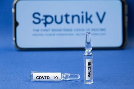 Krasnodar, Russia - January 12, 2021: Coronavirus vaccine in ampoules with the Sputnik V logo background. Sputnik V produces and distributes a vaccine for COVID-2019 Editorial