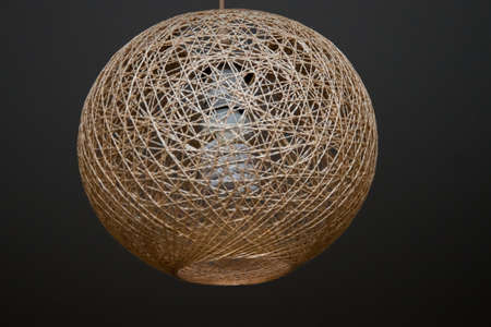 hanging from the ceiling is a decorative lampshade made of twine, with an energy-saving lamp turned on. Chandelier made of braided rope Standard-Bild