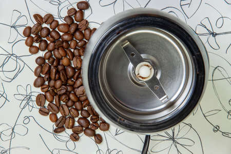 An electric coffee grinder next to a handful of roasted coffee beans. Top view. The concept of freshly brewed coffee