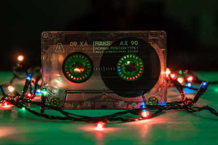 Krasnodar, Russia - March 11, 2021: An old, scratched RAKS audiotape stands on a green background, festooned with multicolored lights. Close-up