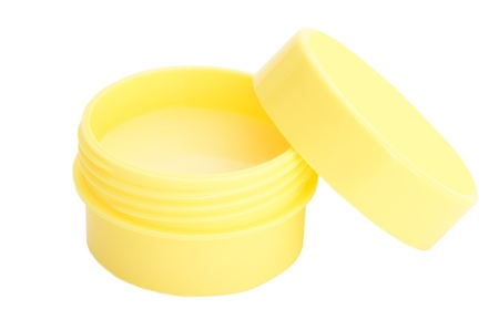 Lip balm in a yellow pot isolated on white background