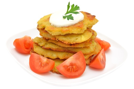 Potato pancakes with slices of tomato on a plate, isolated on white background photo