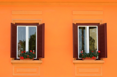 Two windows with flowers on colorful wall in medieval Sighisoara, Romania photo