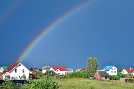 Rainbow over the houses in the countryside