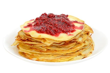 Pancakes with raspberry jam on a plate isolated on white background